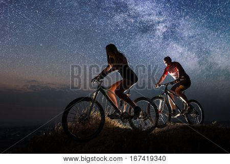 Sporty Couple Riding A Bicycles At Night Under Starry Sky