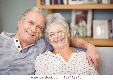 Portrait of senior couple sitting on sofa at home