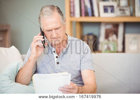 Senior man using mobile phone while looking documents at home