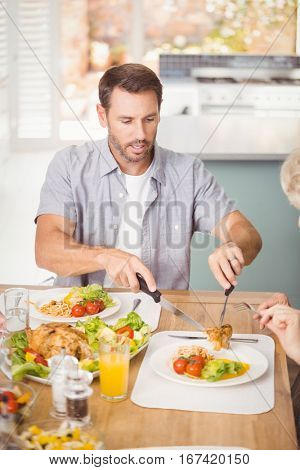 Man serving meat in plate while having lunch with family at home