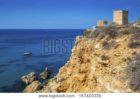 Malta - Sail boat at Ghajn Tuffieha tower on a hot summer day with crystal clear blue sea water