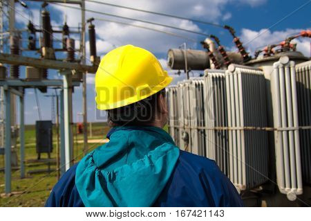 Engineer is checking high voltage transformer station