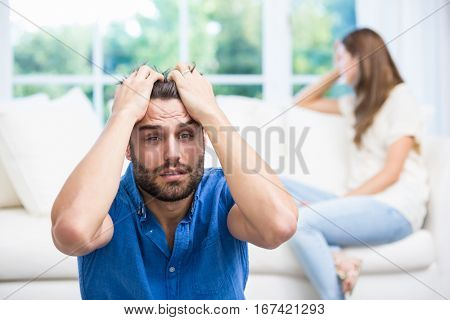 Upset man with hands on head after argument with wife at home