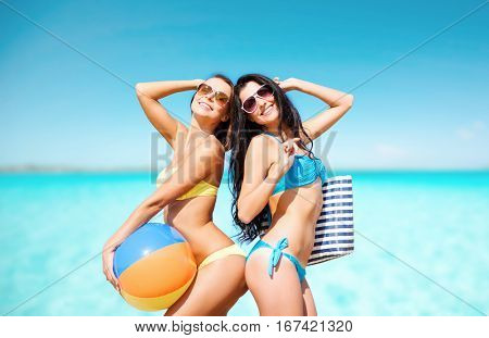 summer holidays, travel, people and vacation concept - happy young women in bikinis and shades posing with inflatable ball and bag over sea beach background