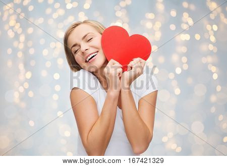 love, charity, valentines day and people concept - smiling young woman or teenage girl with blank red heart shape over holidays lights background