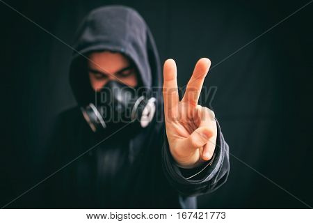 Victory Sign By A Hooded Man On Black Background