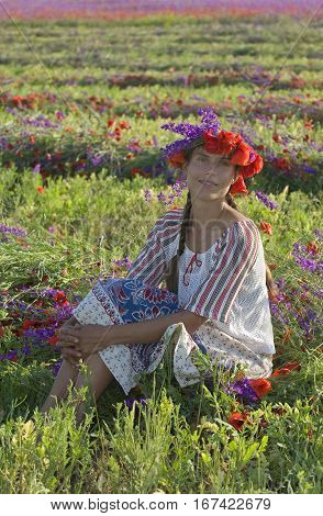 Woman has flowers chaplet on her head. Blossom meadow in background.