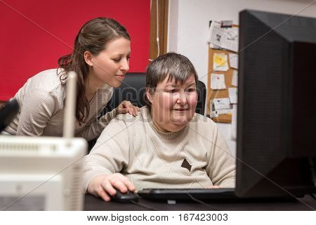 Caregiver And Mentally Disabled Woman Learning At The Computer