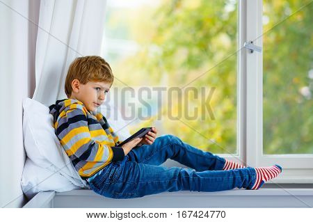 Happy little school boy reading book or ebook by window with yellow autumn foliage at home. Child making his homework for preschool. Education, reading, interest, hobby concept.