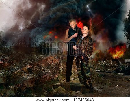 girl and man in military camouflage uniforms among the ruins of a fire in the background.