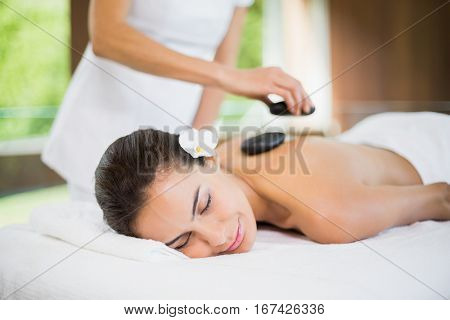Close-up of young woman receiving stone massage at health spa