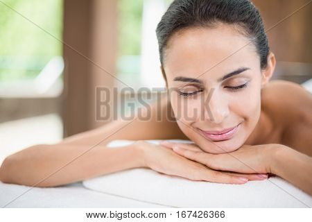 Close-up young woman smiling while relaxing on massage table at spa