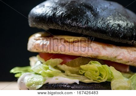 Dark bun hamburger. Lettuce leaves, meat and sauce. Finest ingredients and special recipe.