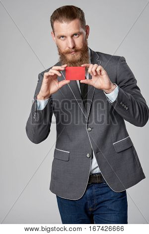 Hipster business man with beard and mustashes in suit standing over grey background showing blank credit card