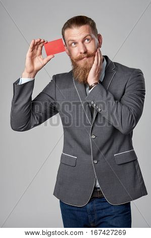 Surprised hipster business man with beard and mustashes in suit standing over grey background showing blank credit card looking up in amazement with hand on cheek.