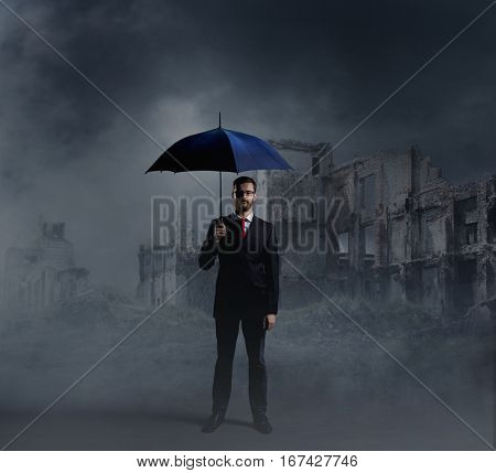 Businessman with umbrella standing over apocalyptic background. Crisis, default, setback concept.