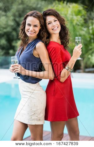 Portrait of happy female friends holding champagne flutes at resort