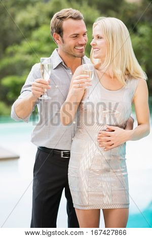Smiling couple holding champagne flutes while standing at poolside