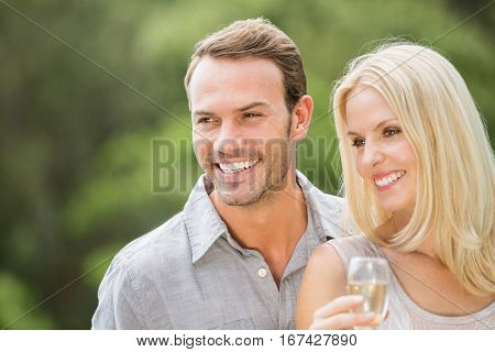 Smiling couple looking away with woman holding champagne flute