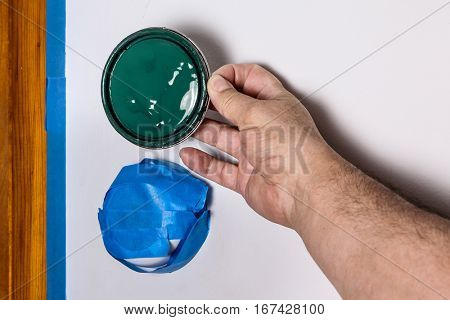 Hand holding green paint top against wall with blue masking tape