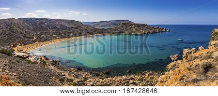 Malta - Panoramic view of Ghajn Tuffieha sandy beach with sail boat blue sky and crystal clear green sea water
