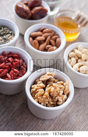 Grain free oat free paleo granola ingredients: mixed nuts seeds goji berries chia honey and coconut oil selective focus
