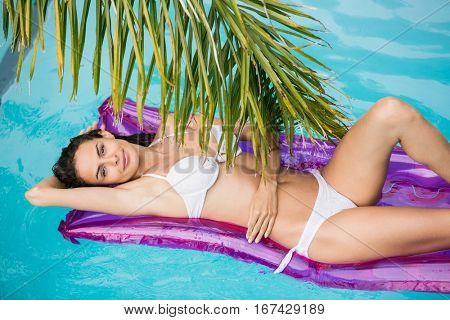 Portrait of attractive young woman relaxing on inflatable raft at swimming pool