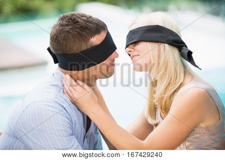 Blindfolded couple kissing while sitting at poolside