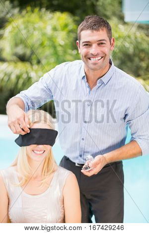 Portrait of smiling man blindfolding woman at poolside
