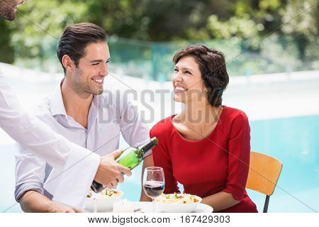 Waiter serving red wine to couple at poolside