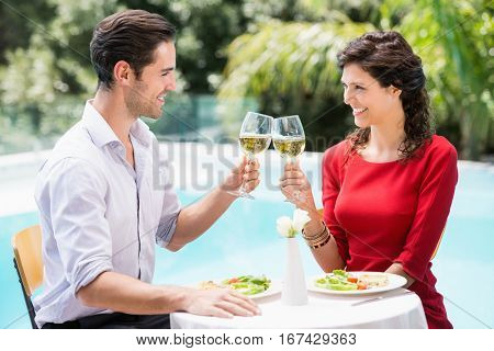 Cheerful couple toasting white wine while sitting at poolside