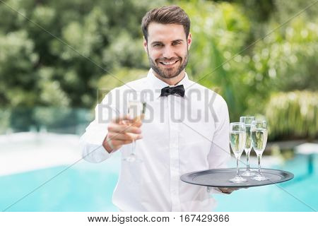 Portrait of smiling waiter offering champagne at poolside