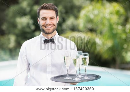 Portrait of smiling waiter carrying champagne flutes on tray at poolside