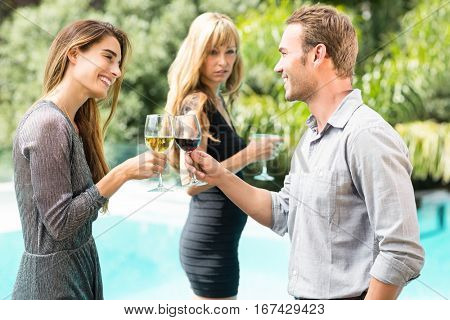 Jealous woman looking at happy couple toasting wine during party