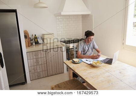 Teenage boy wearing headphones using technology in a kitchen