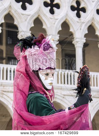 VENICE, ITALY - FEBRAURY 1: Carnival of Venice beautiful mask with fan in front of Doge Palace FEBRUARY 1, 2016 in Venice, Italy