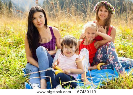 Asian woman with child along with his caucasian girlfriend and her daughter on a picnic in the mountains on a Sunny day