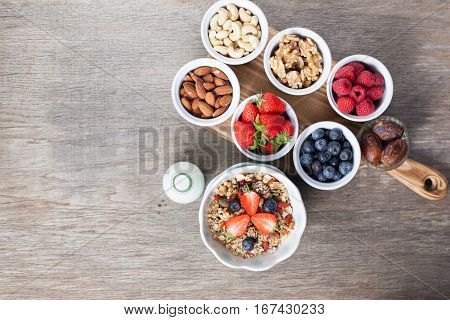 Paleo style breakfast: grain free oat free granola with almond milk and with mixed nuts and fresh berries, top view, selective focus
