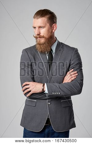 Confident thinking business man with beard and mustashes in suit standing with folded hands looking out of frame in thoughts over grey background