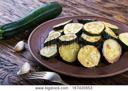 Fried zucchini in a clay plate on a wooden table. raw zucchini and garlic.