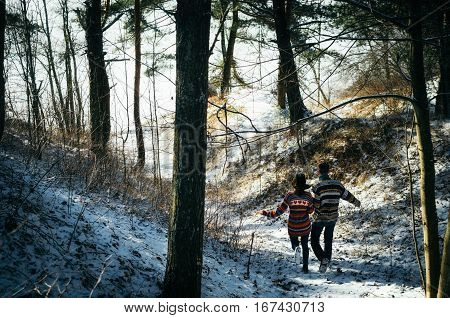 Couple holding hands run away to the forest in winter