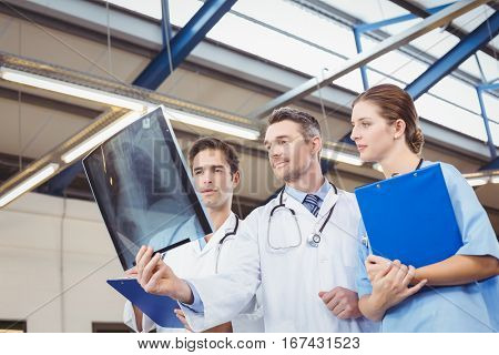 Concentrated doctors examining X-ray while standing at hospital
