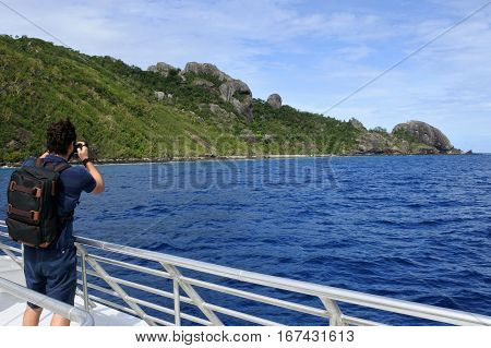 Travel photographer photographing the landscape of a tropical island in the Yasawa group in Fiji from a boat. Real people copy space