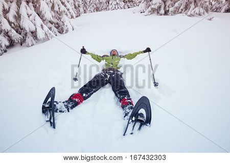 Man wearing snowshoes lies in the snow relaxing and having fun during winter adventure. Toned image wide angle.