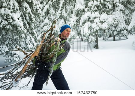 Man With Smiling Face, Drags An Armful Of Firewood