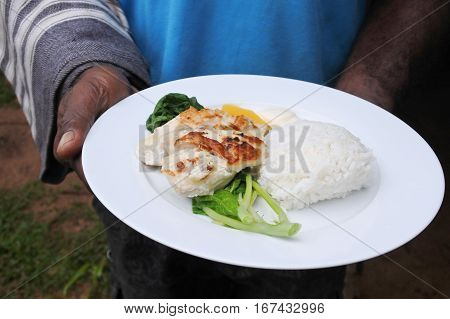 Indigenous Fijian Man Serve Seafood And Vegetables Dish
