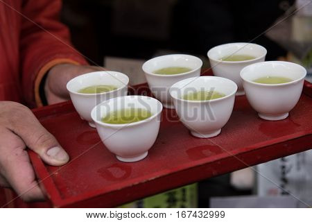 In the picture we can see a man holding a tray with six cups to serve hot green tea. Green tea is very popular in Japan.