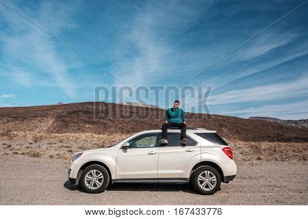 Man sitting on car roof at highway shoulder in Death Valley National Park. California, USA.