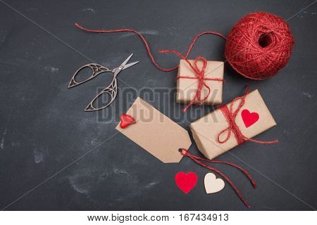 Handmade gift, heart, scissors and tangle of thread on blackboard. Valentine's Day. Space for your text