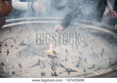 In the picture we can see a big tray with sand and many people are burning incense sticks inside the tray. People are seen worshipping on the background.